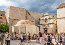 Church of Saint Saviour  and Onofrio`s Fountain in a sunny day i. DUBROVNIK, CROATIA - JULY 16th, 2016: Stradun street starting square in Old Town with the Stock Images