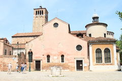 Church of San Giacomo dall'Orio. With cross on round roof in Venice (Italy) with tower, dwell and tourists Stock Image