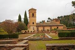 Church of Santa Maria de Alhambra, Granada, Spain, on a cloudy day. Church of Santa Maria de Alhambra, Granada, Spain, with Jardins del Paraiso garden in front stock image