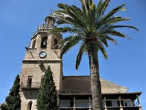 Church of Santa Maria la Mayor, Ronda, Andalucia, Spain. Clock tower on the Church of Santa Maria la Mayor and a palm tree against a clear blue sky at Ronda royalty free stock images