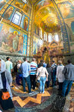 Church of the Savior on Spilled Blood. crowd of tourists in fro. ST PETERSBURG, RUSSIA - JULY 14, 2016: Interior of Church of the Savior on Spilled Blood stock photos
