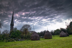 Church in scenic countryside. Scenic view of church in picturesque countryside under overcast cloudscape Stock Images