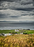 Church by the sea. Barley in the foreground blue sea and dark irish clouds Stock Image