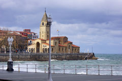 Church with sea 2. Elegant church in an Asturian town with sea, waves and grey sky Stock Images