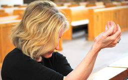 Church service. Mature female blond beauty attending church service royalty free stock photography