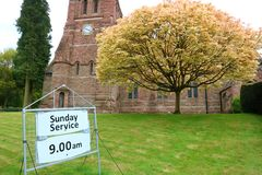 Church and service sign. Chetwynd church with Sunday service sign in foreground royalty free stock photos