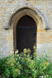 Church side door with wild flowers Stock Photos