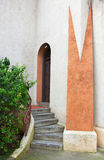Church side entrance. Curved staircase to arched small church door on beige and brown stucco building Stock Photo