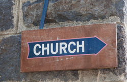 Church Sign. Old brown wood church sign with blue arrow on dark stone wall royalty free stock photo
