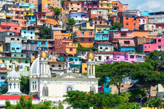 Church and Slum. White church with a colorful slum on a hill rising above it in Guayaquil, Ecuador Royalty Free Stock Images