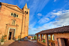 Church and small square. Monticello D'Alba, Italy. Red brick catholic church on small cobbled square under beautiful blue sky with white clouds in town of Stock Image