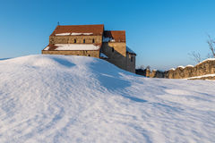 Church on a snowy hill. Winter landscape of a Transylvanian church in a fortress in Sibiu County royalty free stock images
