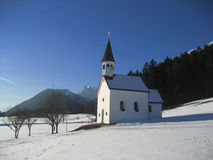 Church on snowy mountainside. Scenic view of small remote church on snowy mountainside with forest in background, Tirol, Austria Stock Photography