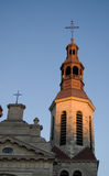 Church spire and cross. View of church spire and cross, along with steeple, highlighted by dusk sunlight against a clear blue sky; Quebec City, Canada stock image