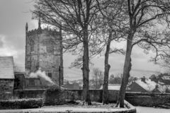 Church spire or tower with roof tops of houses with snow. royalty free stock photo
