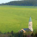 Church in spring meadows; Erzgebirge. Erzgebirge mountains in May; fresh green fields rising up the hill and a local church Stock Photo