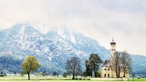 The Church St. Coloman while snowing. The winter landscape, Schwangau, Germany. Snowy mountains stock video footage