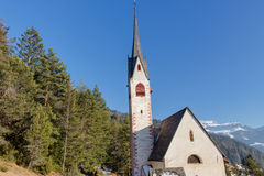 Church of St. Jacob overlooking pine forests and snow-capped pea Royalty Free Stock Photo