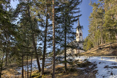 Church of St. Jacob overlooking pine forests and snowy fields in Royalty Free Stock Photos