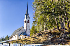 Church of St. Jacob overlooking pine forests and snowy fields in Royalty Free Stock Photo
