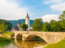 Church of St John the Baptist and old stone bridge at Lake Bohinj in alpine village Ribicev Laz, Julian Alps, Slovenia.  Stock Image