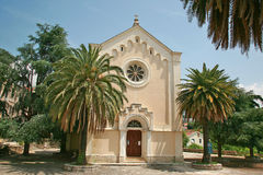 Church of St. Leopold Mandic, Montenegro. The Catholic Church, with the traditional window-rosette above the entrance surrounded by palms and trees, the size Stock Images