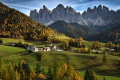 Church of St. Magdalena in front of the Geisler or Odle Dolomites mountain peaks. Val di Funes valley in Italy. stock photo