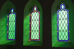Church stained glass windows. Beautiful green reflected light coming through a churchs stained glass windows Royalty Free Stock Photos