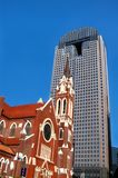 Church Stands Firm in Face of Progress. Old Church building stands in front of a skyscraper in downtown Dallas, Texas.  Blue sky frames tall office building Stock Images