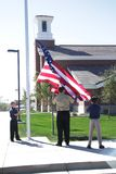 Church and State. Two cub scouts and their leader raise an American flag in front of a church Royalty Free Stock Photography