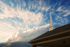 Church Steeple against a cloudy sky. A church steeple in a cloudy sky at sunset Royalty Free Stock Photo