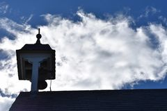 Church steeple and bell tower silhouette against silver cloud Royalty Free Stock Photos