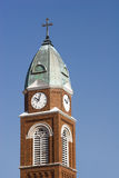 Church Steeple and Clock. A church steeple with clock and cross Royalty Free Stock Photography