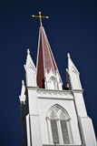 Church Steeple and Cross. Church Steeple and Golden Cross, brightly lit, against deep blue sky Stock Photo