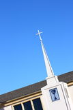 Church Steeple with Cross. A tall slender Church steeple with a white cross at the top, photographed against a bright blue sky Stock Image