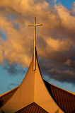 Church Steeple Cross. A Church Steeple Cross glows gold at sunset with orange clouds in the background Stock Image