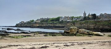 The town of St Andrews, seen from the beach. The church steeple dominates this view of St Andrews by the Sea, the home of Golf.A fancy modern house on the end of royalty free stock photography