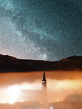 Church steeple in fog with starry night sky