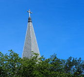 Church Steeple And Green Leaves. Church steeple rising above green leaves against a blue sky Stock Image