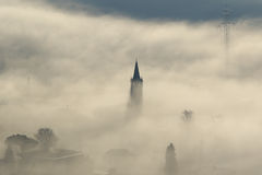 Church steeple, pylons and trees in fog Royalty Free Stock Photography