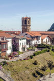 Church steeple of Zarautz. In the Spanish province of San Sebastian, there is a garden with trees and houses of the village. It is a vertical picture on a sunny Stock Images
