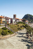 Church steeple of Zarautz. In the Spanish province of San Sebastian, there is a garden with trees and houses of the village. It is a vertical picture on a sunny Royalty Free Stock Photography