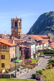 Church steeple of Zarautz. In the Spanish province of San Sebastian, there is a garden with trees and houses of the village. It is a vertical picture on a sunny Stock Photos