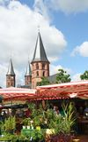 Church steeples, Kaiserslautern, Germany. Three church steeples of the Stiftskirche are framed against a bright blue sky and the stalls of the weekly farmers Stock Photography