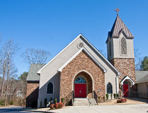 Church with Stone Face and Red Doors. A small church with a stone wall face and red doors under a blue sky Stock Photos