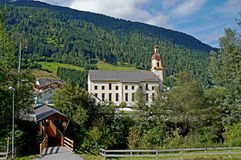 Church in the Stubai Valley in Tyrol. A striking church in the Stubai Valley in Tyrol, a roofed wooden bridge and forested mountains Stock Images