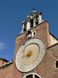 Church and sun. A curch with a special clock seen in Venice Royalty Free Stock Photography