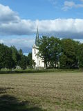 Church. A Swedish church with a high steeple and painted white with a graveyard in the foreground.  It is surrounded by trees and fields and photographed against Royalty Free Stock Images