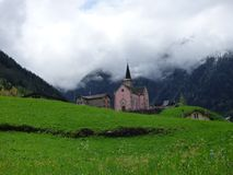 A Church in the Swiss Alps with fog hanging just above the steeple royalty free stock photography