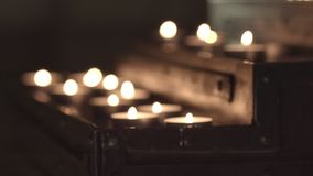 Church table for candles. Focus change out of focus on candles. without color correction, close-up stock video footage